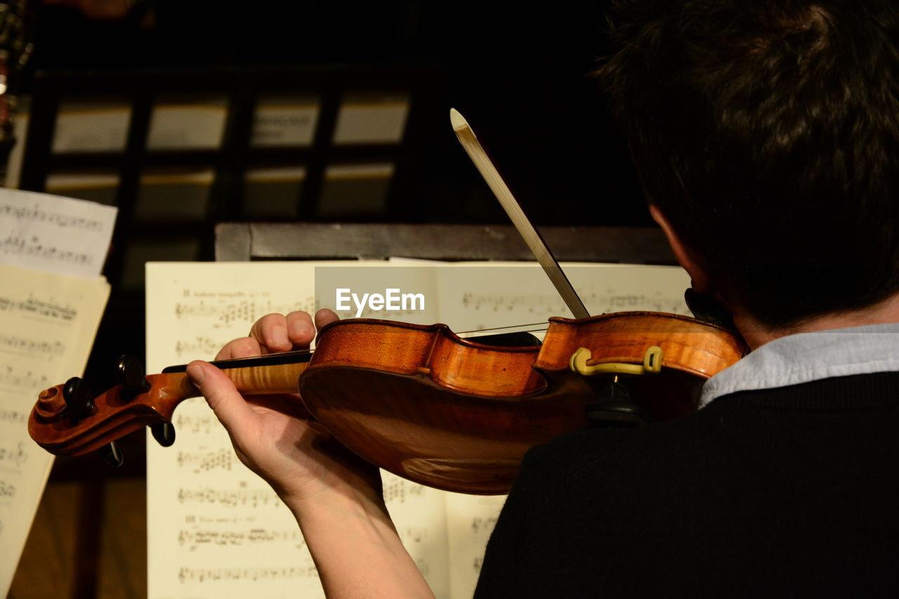 Rear view of man playing violin