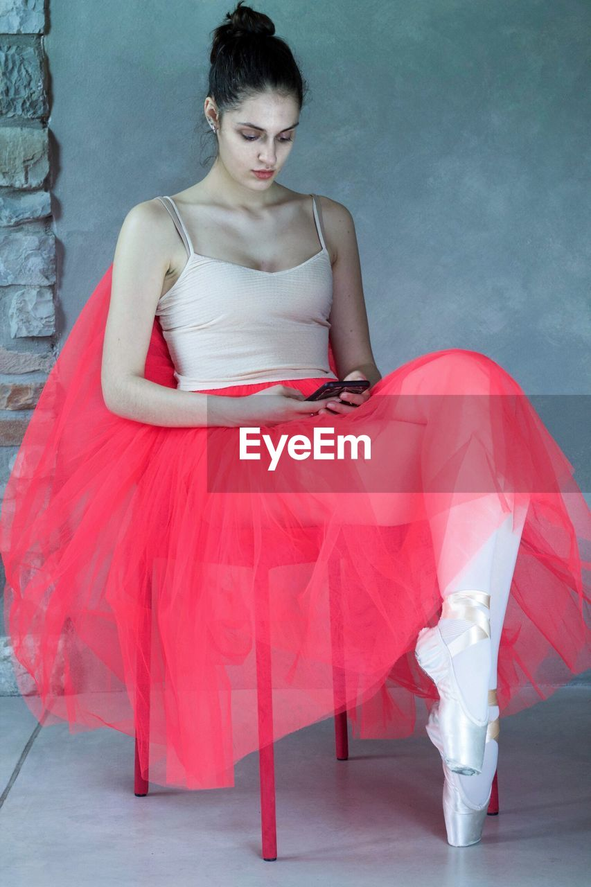 Full length of ballet dancer sitting on chair while using phone