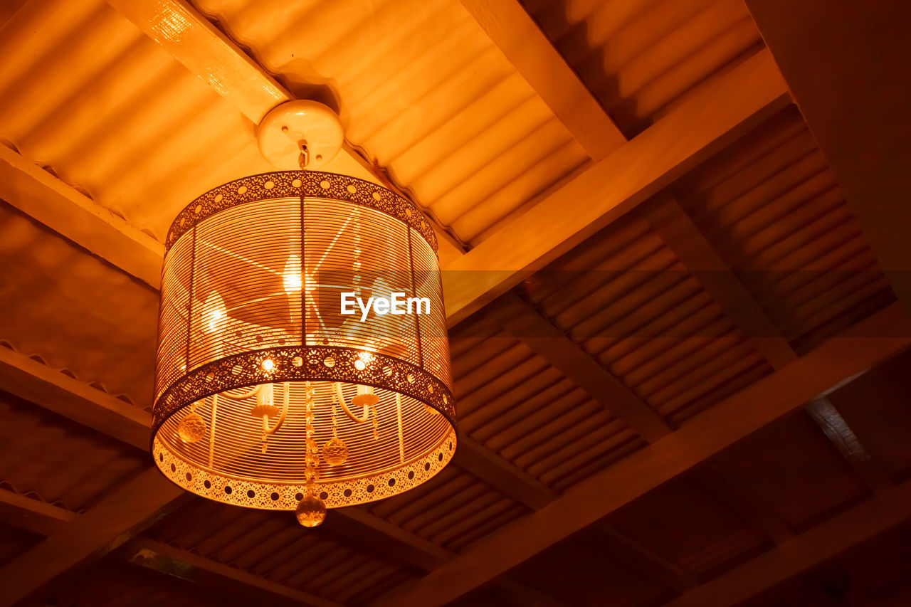 illuminated, lighting equipment, low angle view, indoors, ceiling, light, hanging, no people, pendant light, electric light, glowing, electricity, architecture, built structure, technology, focus on foreground, glass - material, light bulb, pattern, close-up, electric lamp