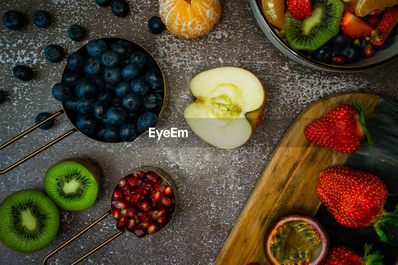 High angle view of fruit assortment in on table in bowl and on cutting board