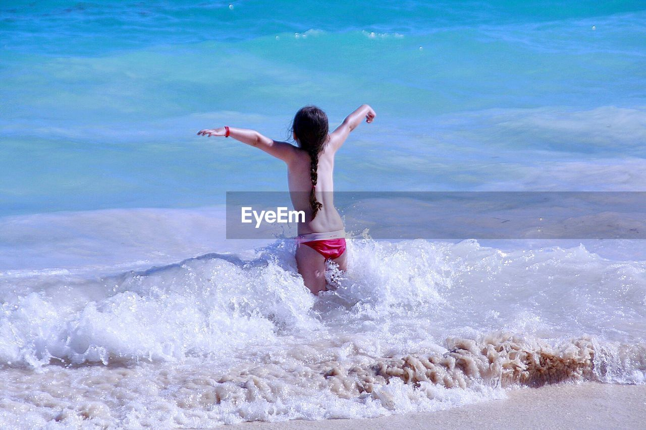 Rear View Of Girl With Arms Outstretched Standing In Sea