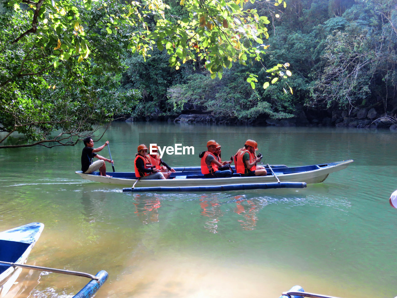 nautical vessel, tree, water, transportation, river, nature, togetherness, real people, oar, leisure activity, mode of transport, men, day, medium group of people, outdoors, sitting, women, adventure, canoe, growth, rowboat, beauty in nature, rowing, rafting, kayak, vacations, lifestyles, adult, people