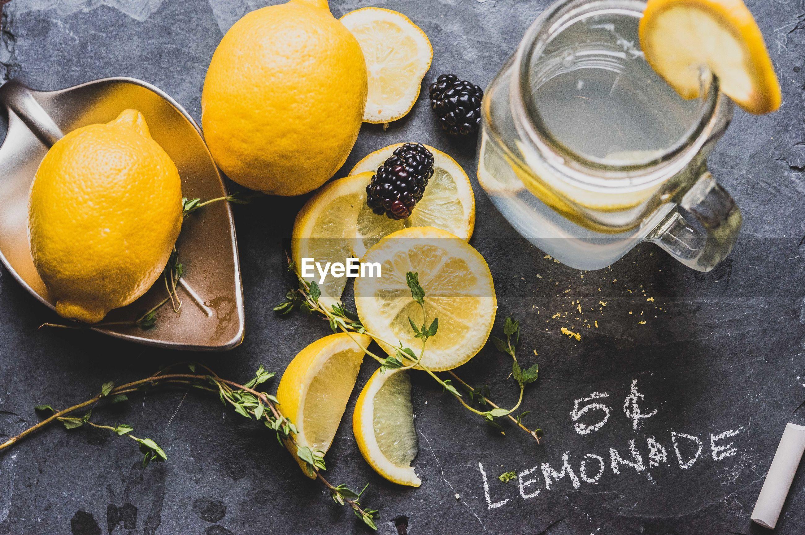 High angle view of lemon by jar on slate