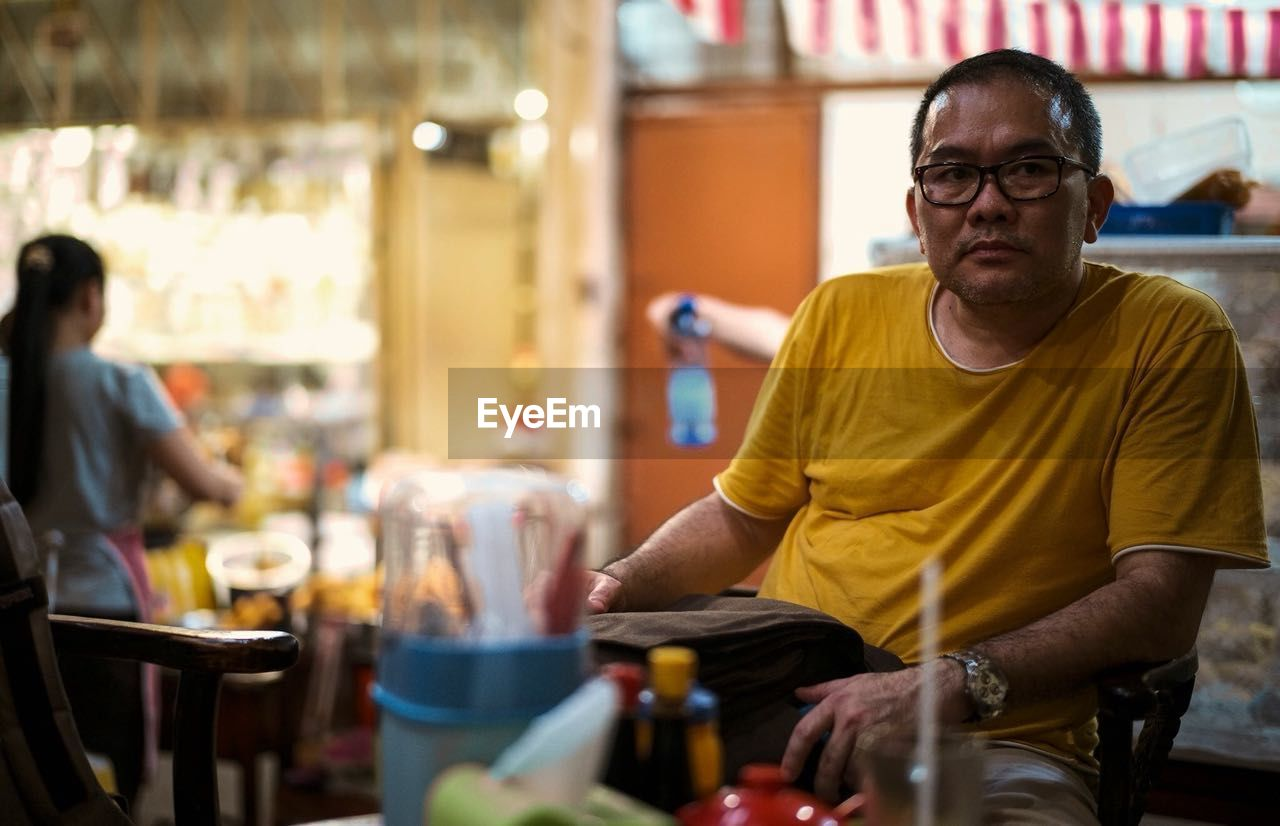 sitting, real people, one person, focus on foreground, indoors, eyeglasses, men, day, one man only, people, only men, adult, adults only