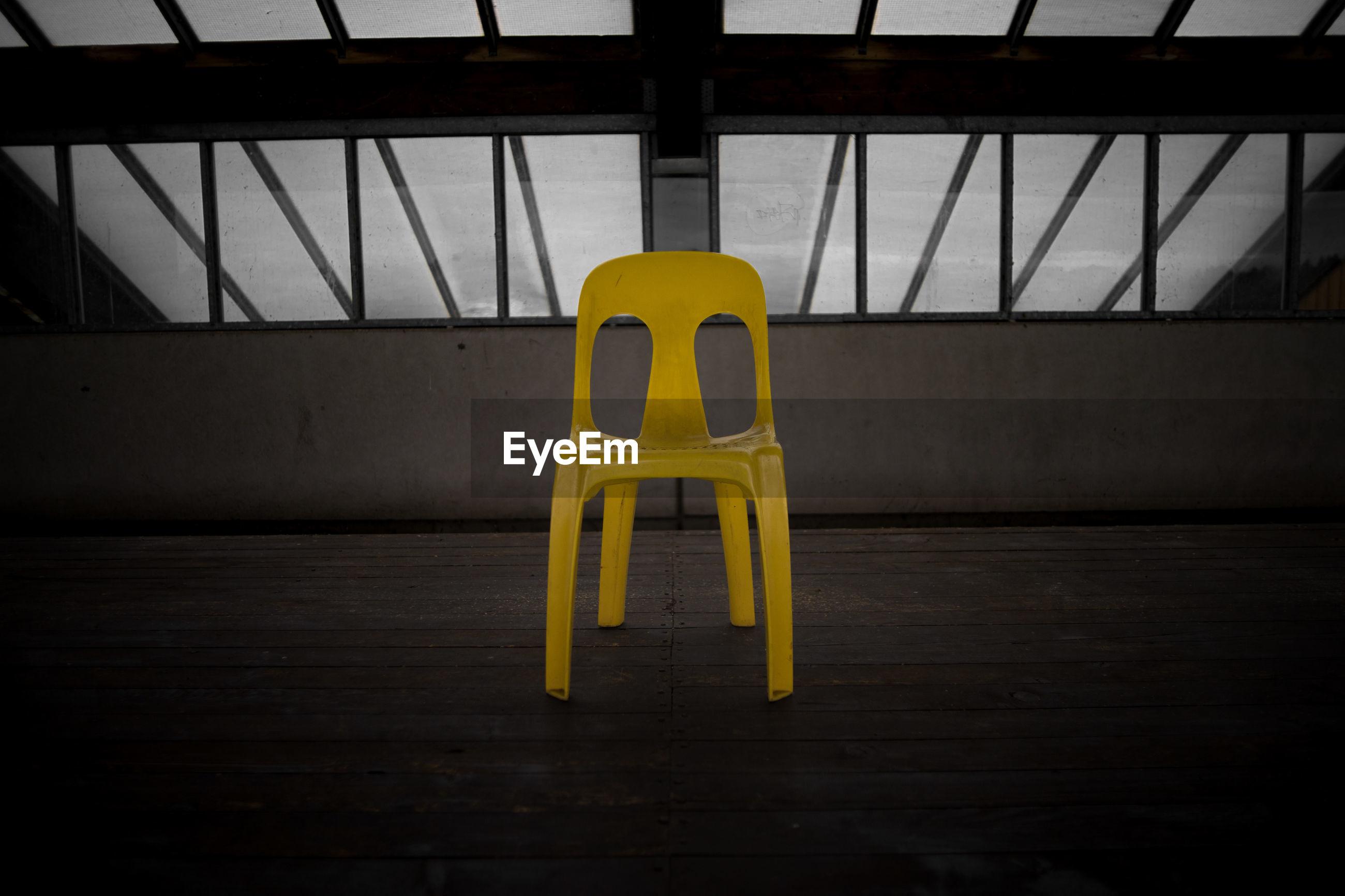 Empty yellow chair on hardwood floor