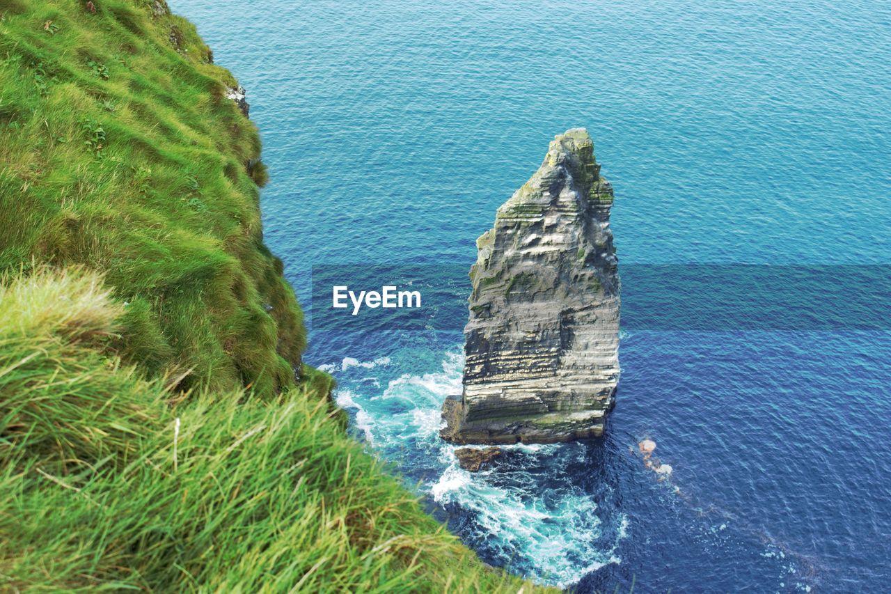 High angle view of headland at calm blue sea