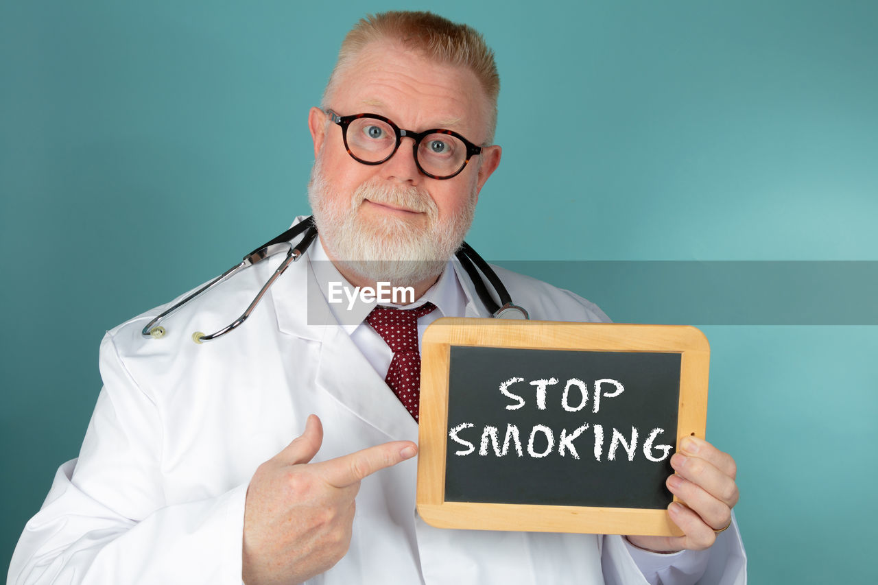 Portrait of doctor showing text on slate against green background