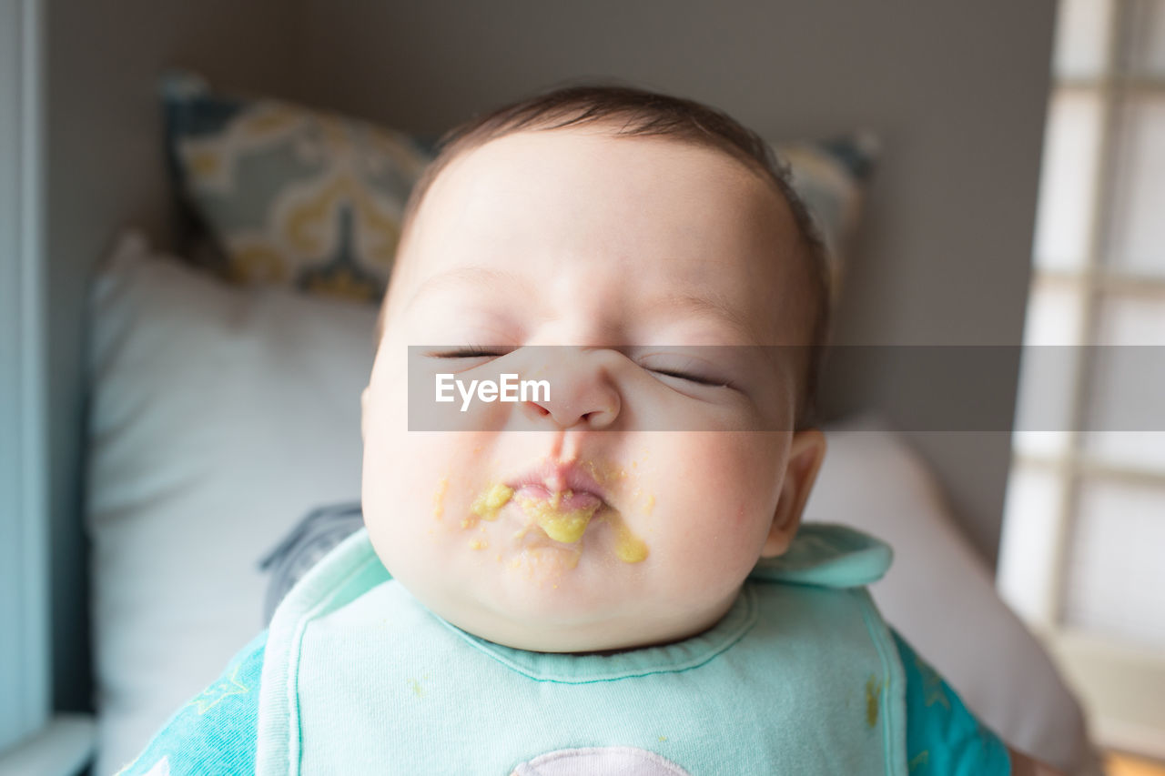 Close-Up Of Cute Baby With Messy Face Sleeping At Home