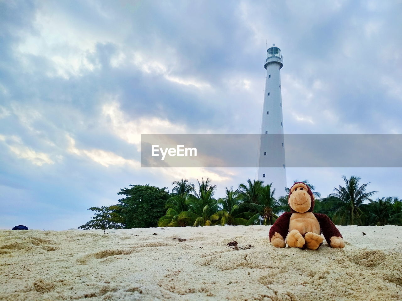 Stuffed toy on sand at beach against lighthouse