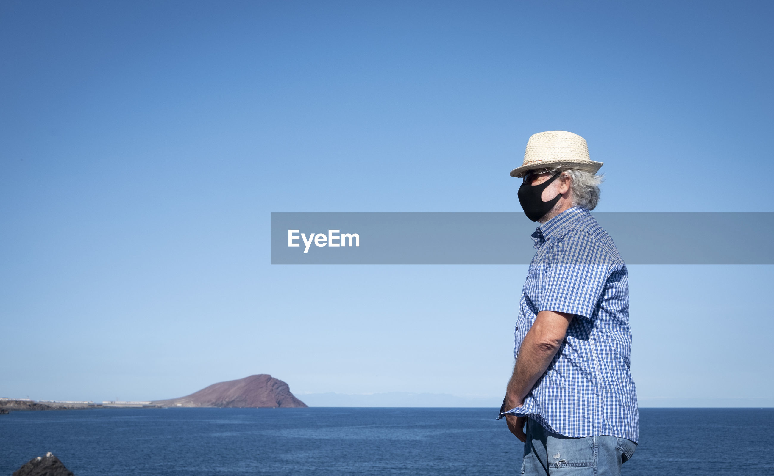 Senior man wearing mask standing by sea against clear sky
