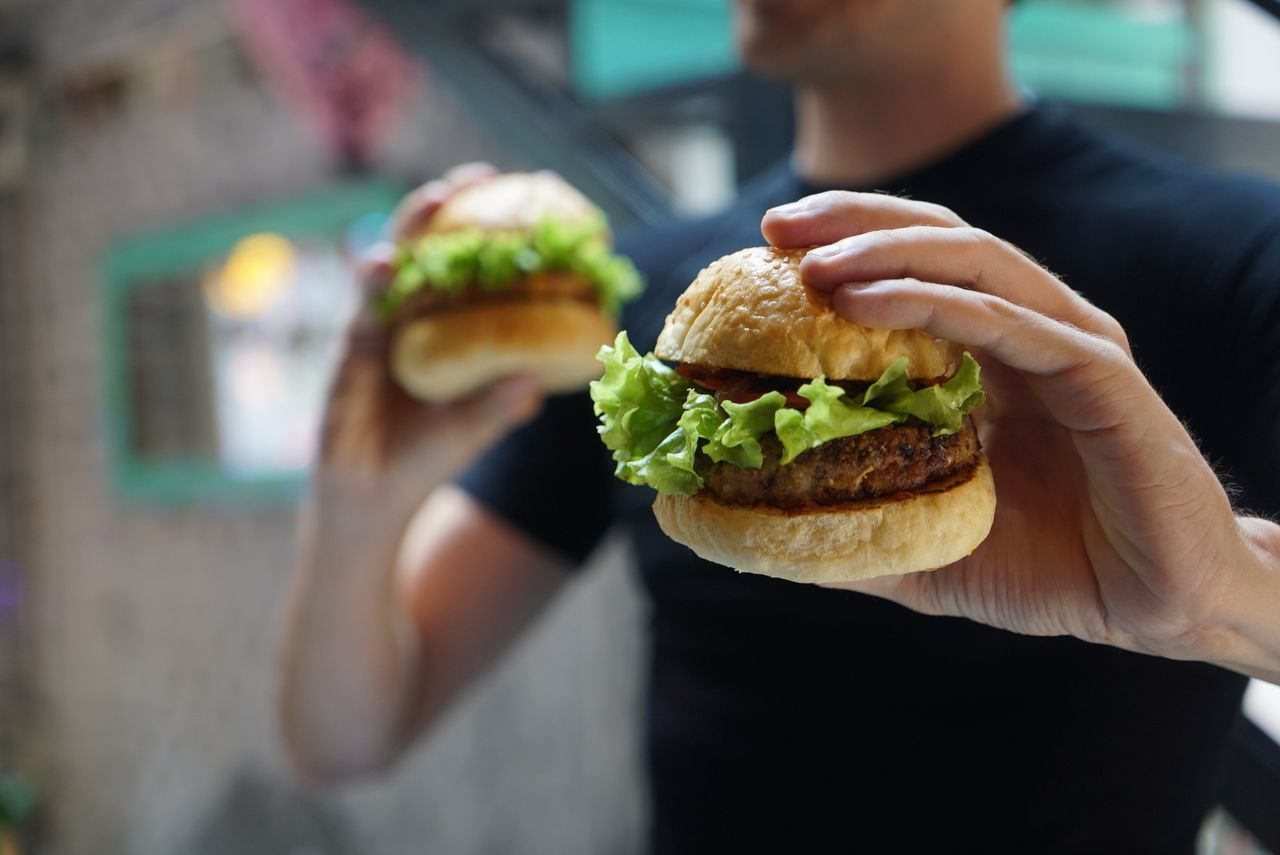Midsection Of Man Holding Hamburgers