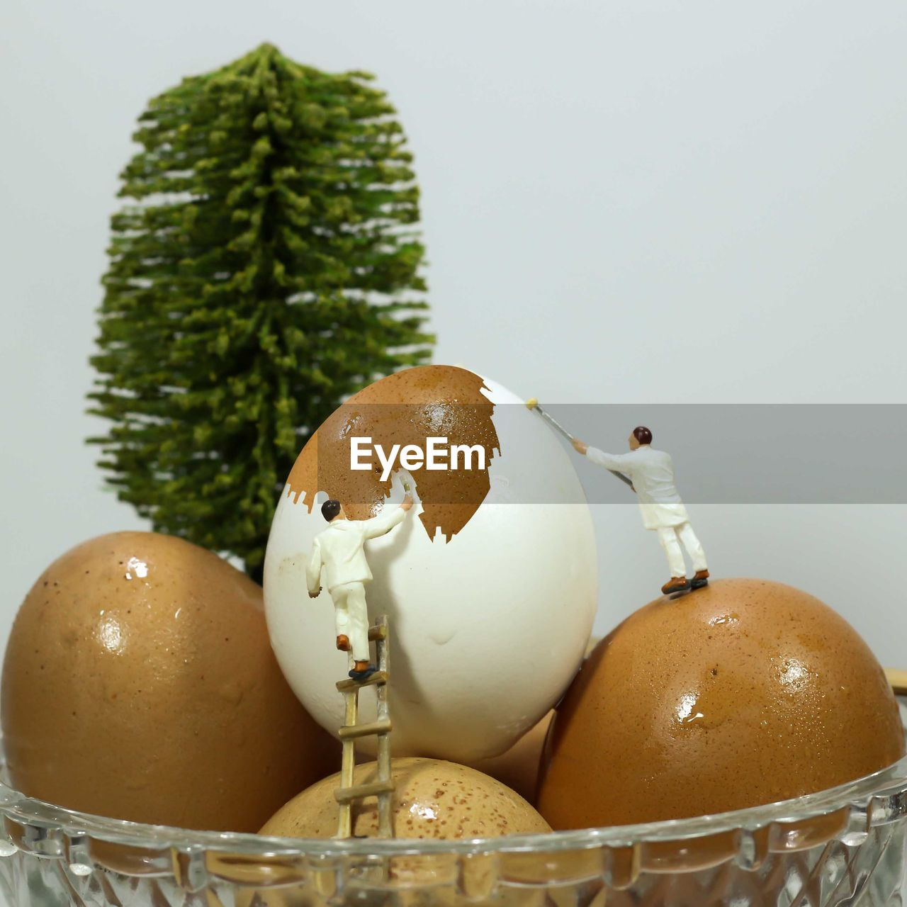 Close-up of figurines with easter eggs against white background