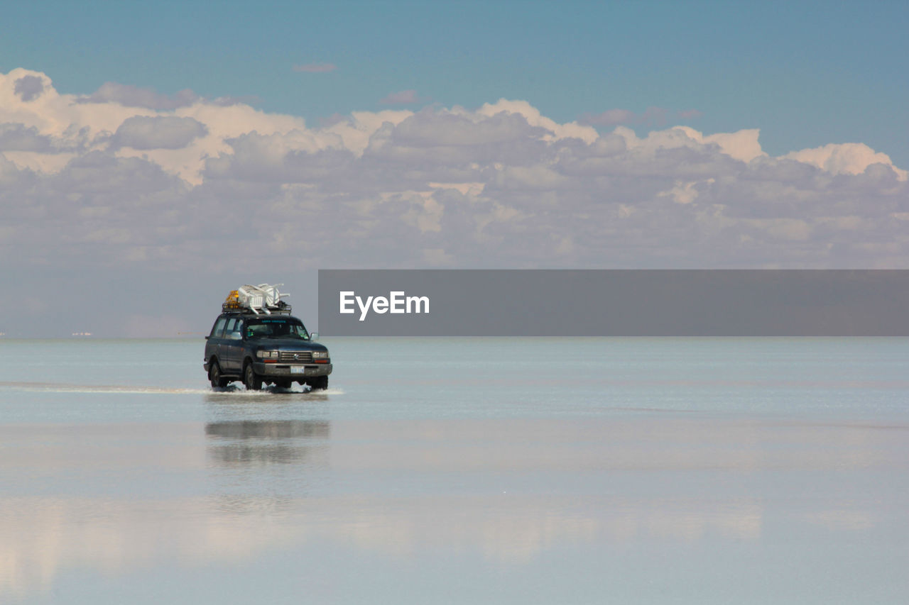 Off-Road Vehicle In Water At Salar De Uyuni Against Cloudy Sky