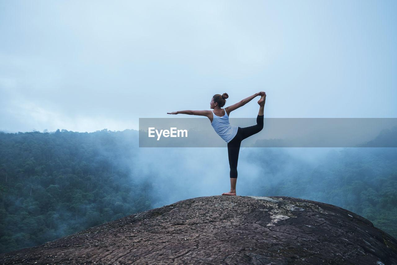 Full length of woman doing yoga on mountain against sky