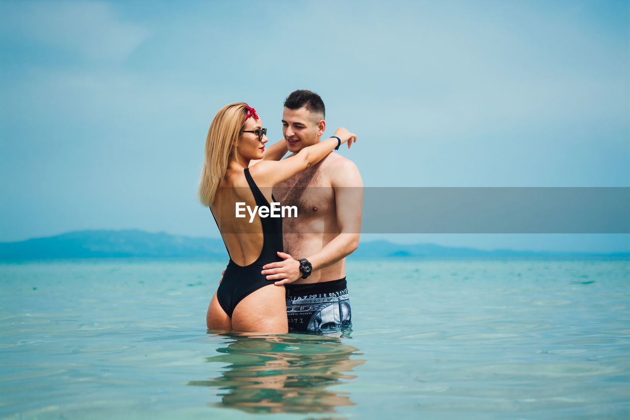 two people, water, men, shirtless, togetherness, love, couple - relationship, lifestyles, young adult, sea, young women, heterosexual couple, leisure activity, adult, emotion, real people, young men, waterfront, positive emotion, outdoors