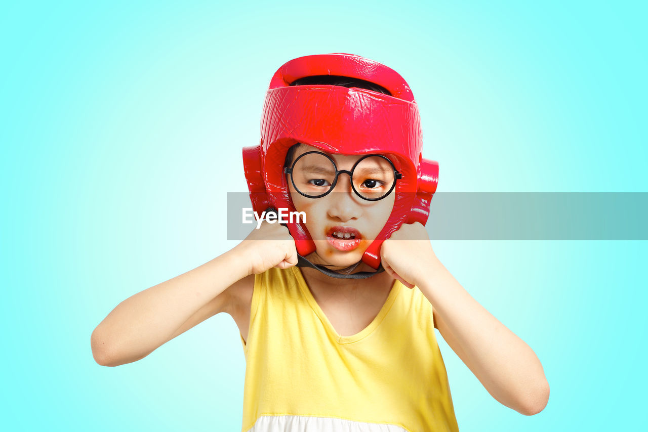 Portrait of boy wearing boxing head protector against blue background