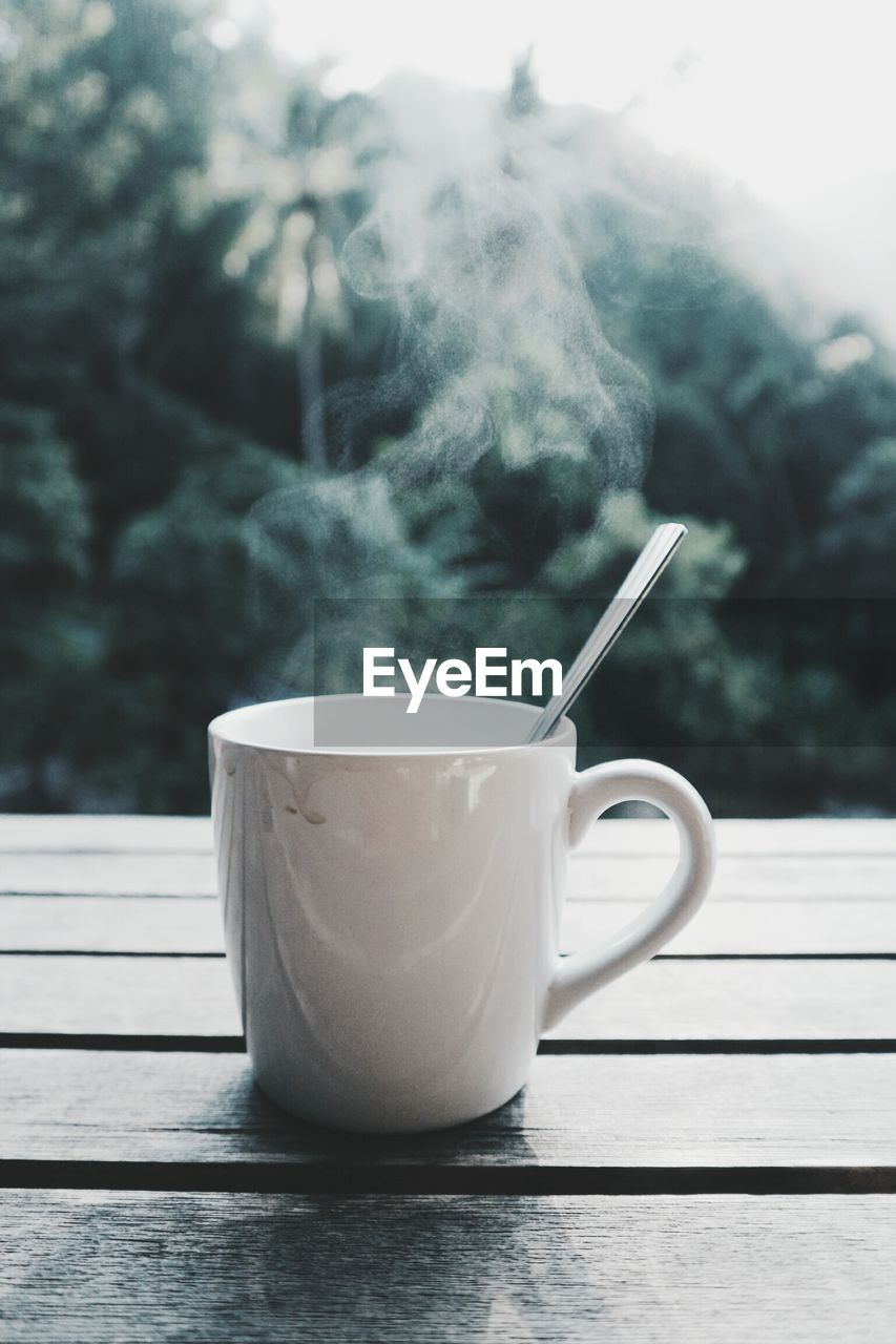 Close-Up Of Steam Emitting From Coffee Cup On Table