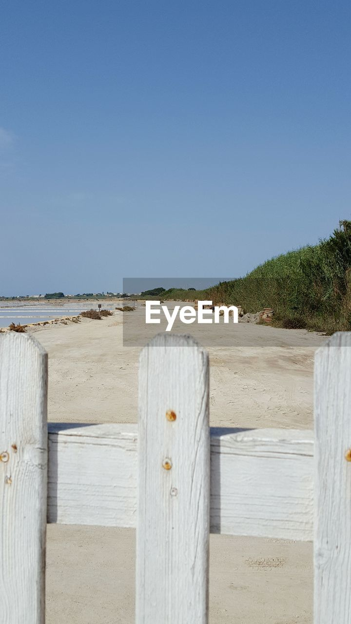 Wooden fence at sandy beach against clear sky
