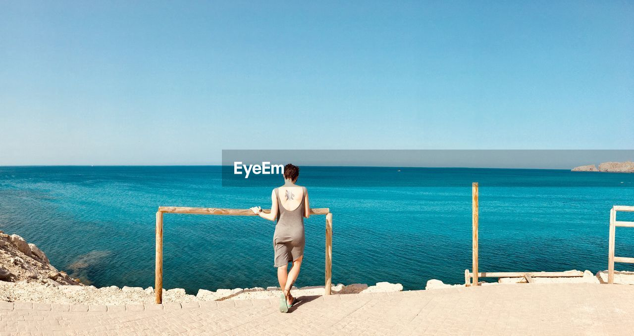 Rear view full length of woman standing against sea on sunny day