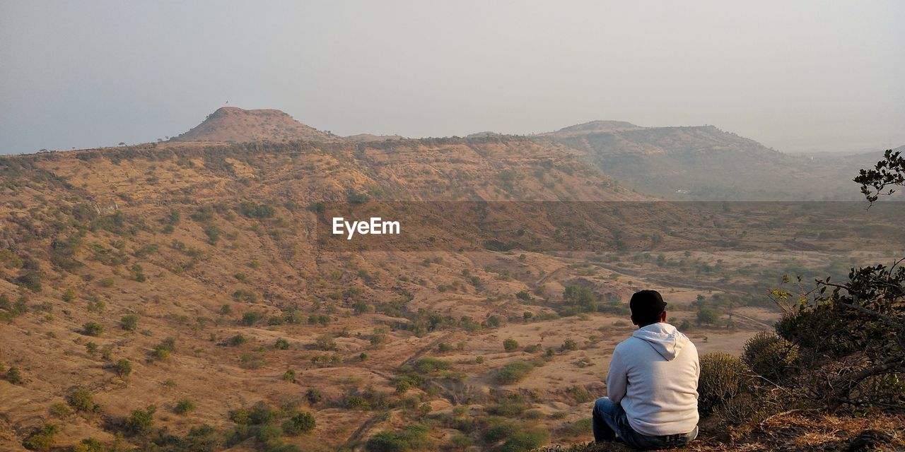 Rear view of young man sitting on mountain against sky
