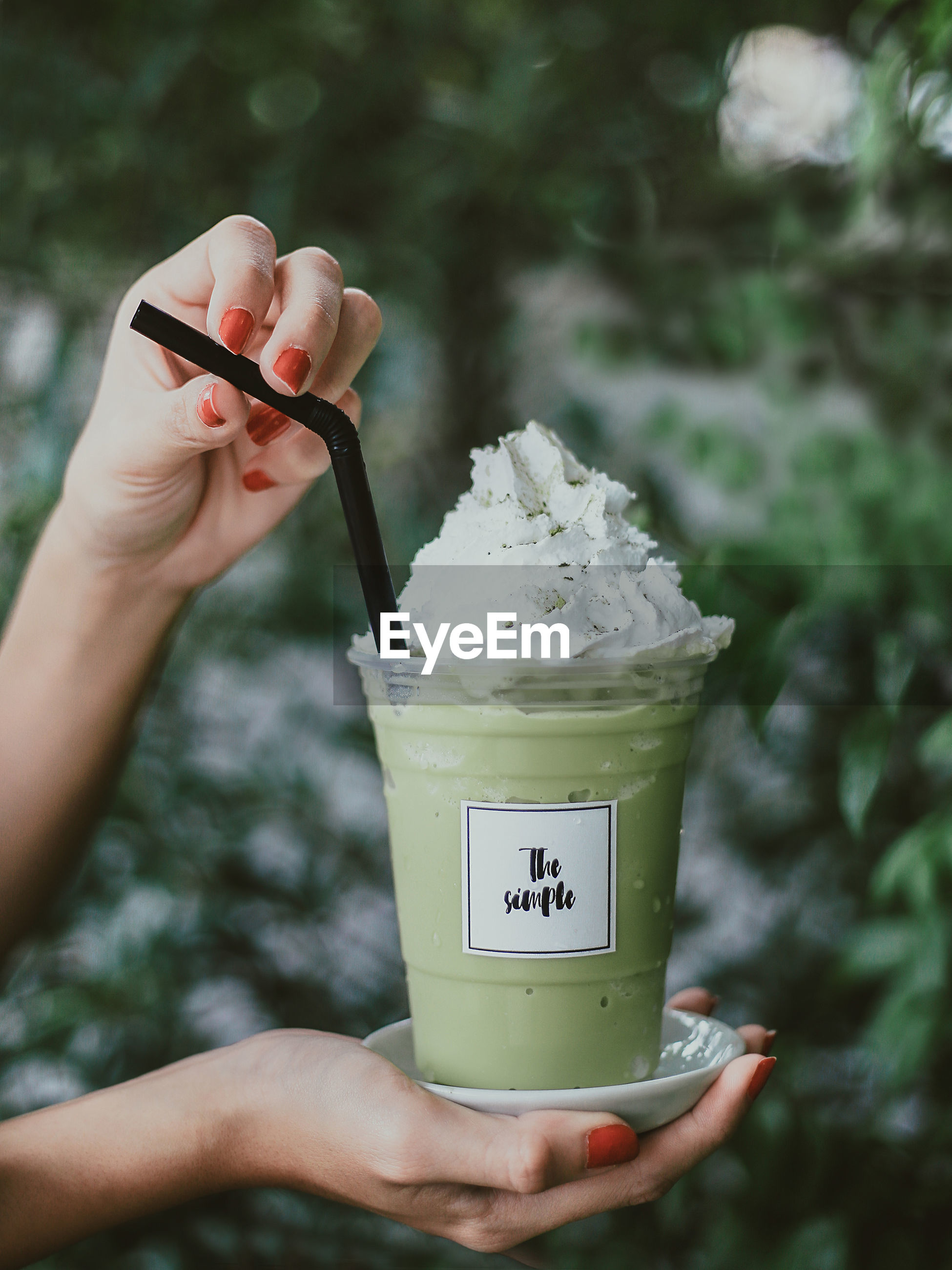 Cropped hands of woman holding drink with whipped cream outdoors