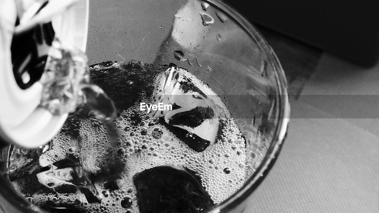 Close-up of can pouring drink in glass