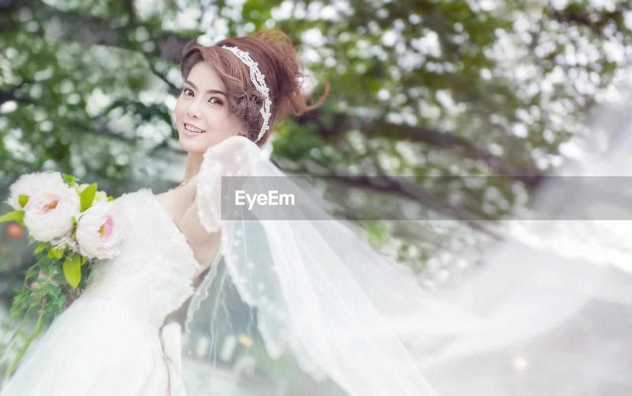 Portrait Of Smiling Bride With Bouquet Holding Veil
