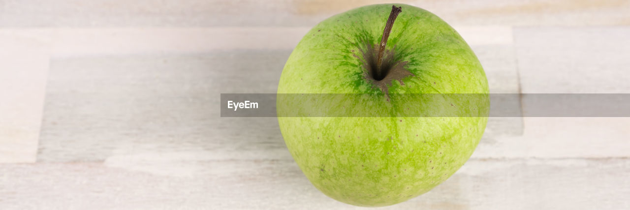 fruit, food and drink, healthy eating, food, wellbeing, green color, still life, freshness, table, no people, indoors, close-up, apple - fruit, focus on foreground, single object, granny smith apple, high angle view, wood - material, studio shot, apple, ripe, temptation