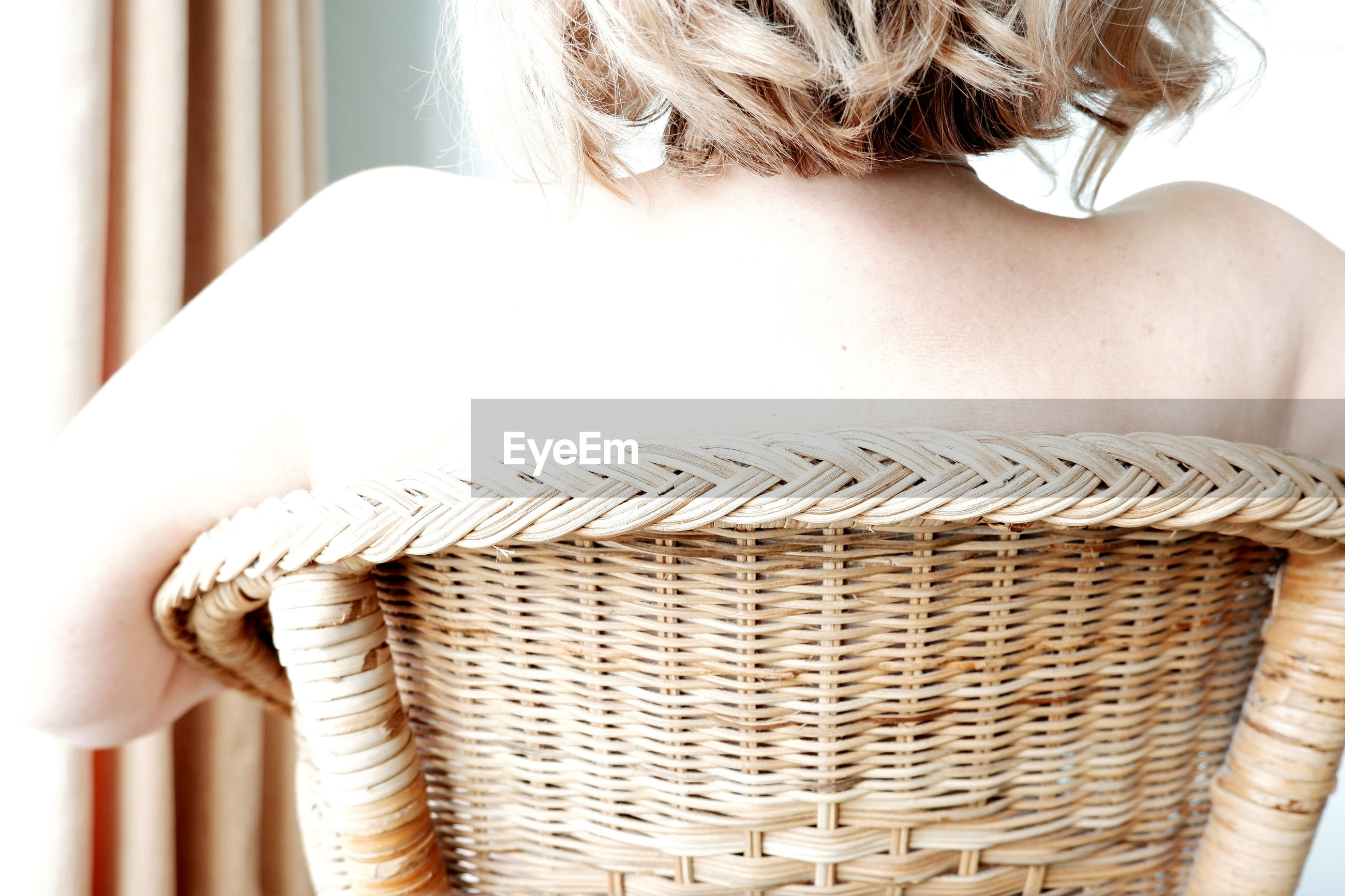 Close-up of woman on wicker chair