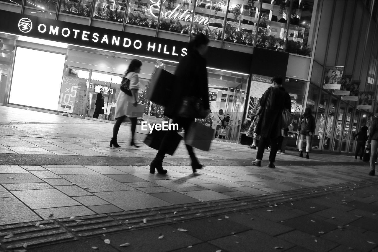 text, blurred motion, real people, walking, transportation, city, architecture, men, illuminated, building exterior, outdoors, day, people