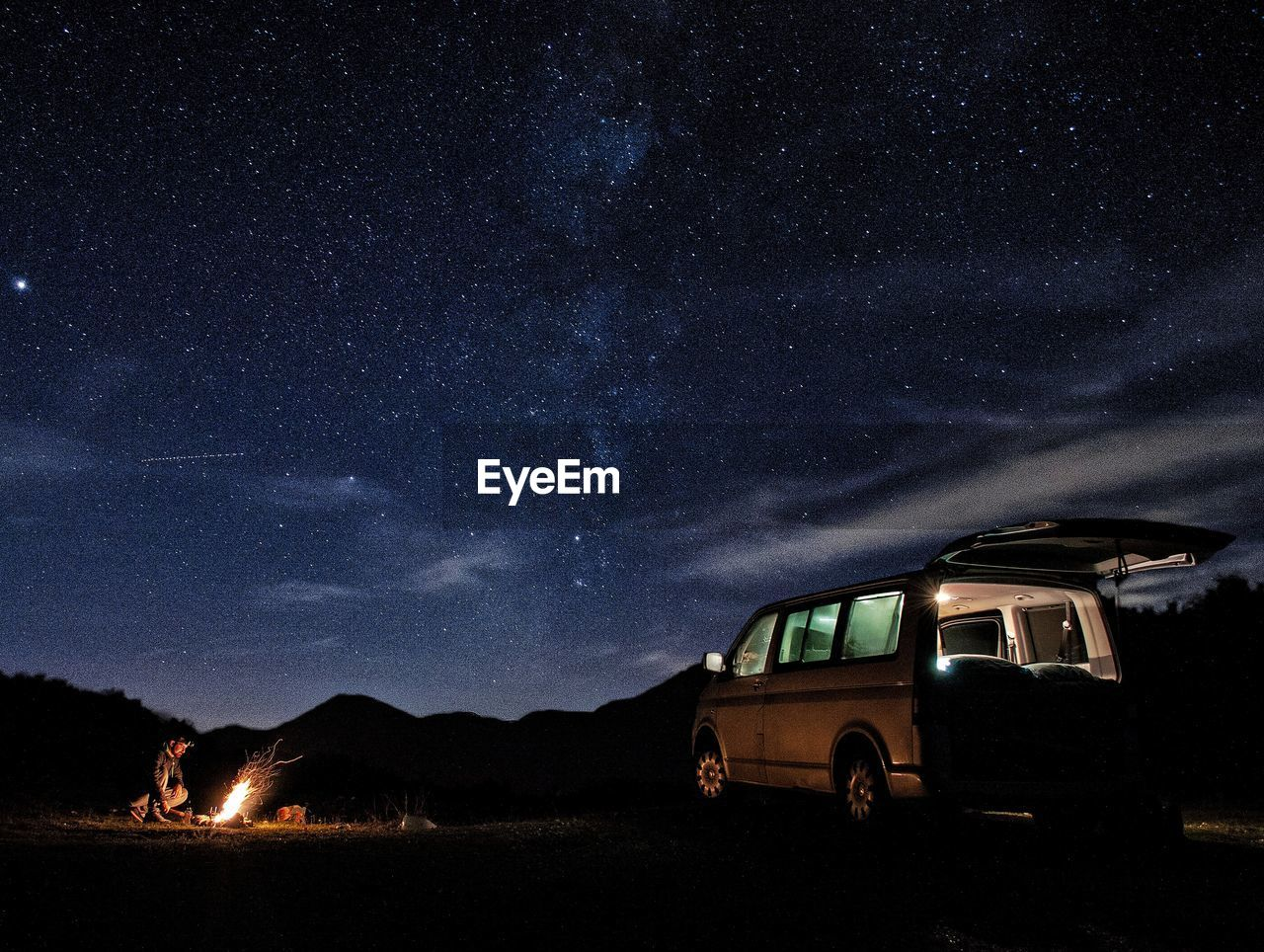 Man With Campfire And Van On Field Against Star Field
