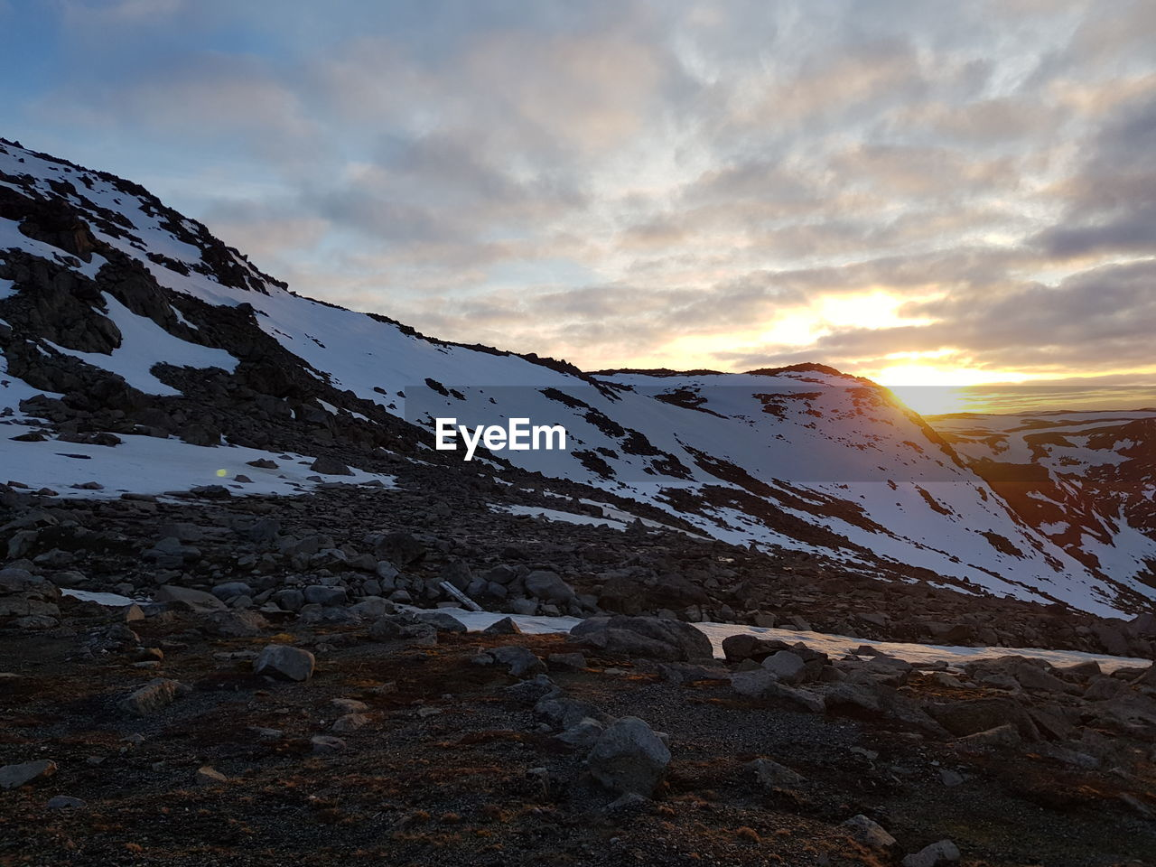 sky, beauty in nature, cold temperature, scenics - nature, winter, cloud - sky, mountain, tranquility, tranquil scene, snow, snowcapped mountain, environment, non-urban scene, nature, mountain range, sunset, landscape, idyllic, rock, no people, outdoors, mountain peak, formation