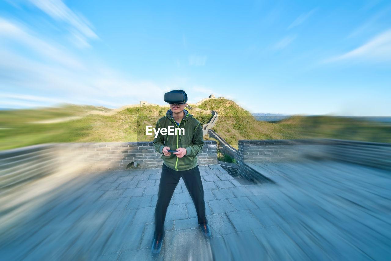 Man enjoying virtual reality simulator while standing on great wall of china