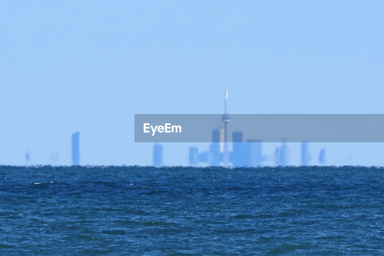 Distant view of cn tower by lake ontario against sky in city