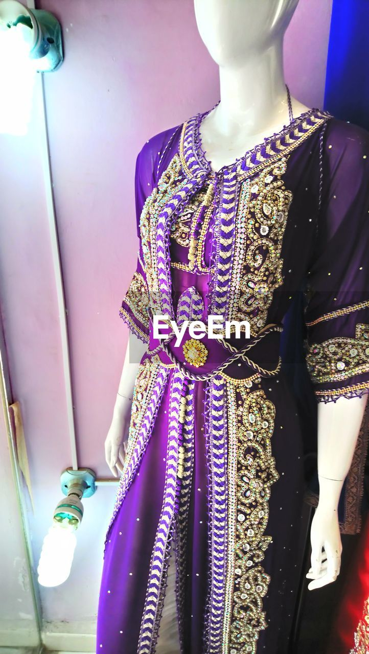 clothing, mannequin, indoors, retail, traditional clothing, fashion, store, dress, multi colored, adult, for sale, jewelry, people, retail display, close-up, human representation, purple, choice