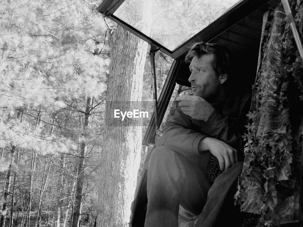 Man looking away while sitting in car trunk at forest