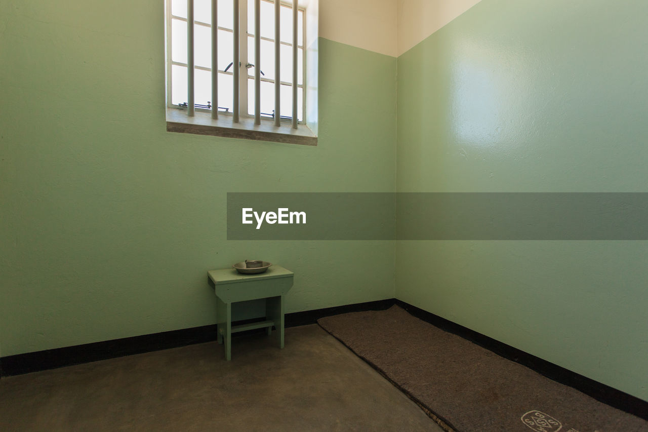 window, indoors, domestic room, absence, wall - building feature, empty, no people, day, architecture, seat, prison, punishment, prison cell, flooring, green color, table, building, sink, furniture, built structure