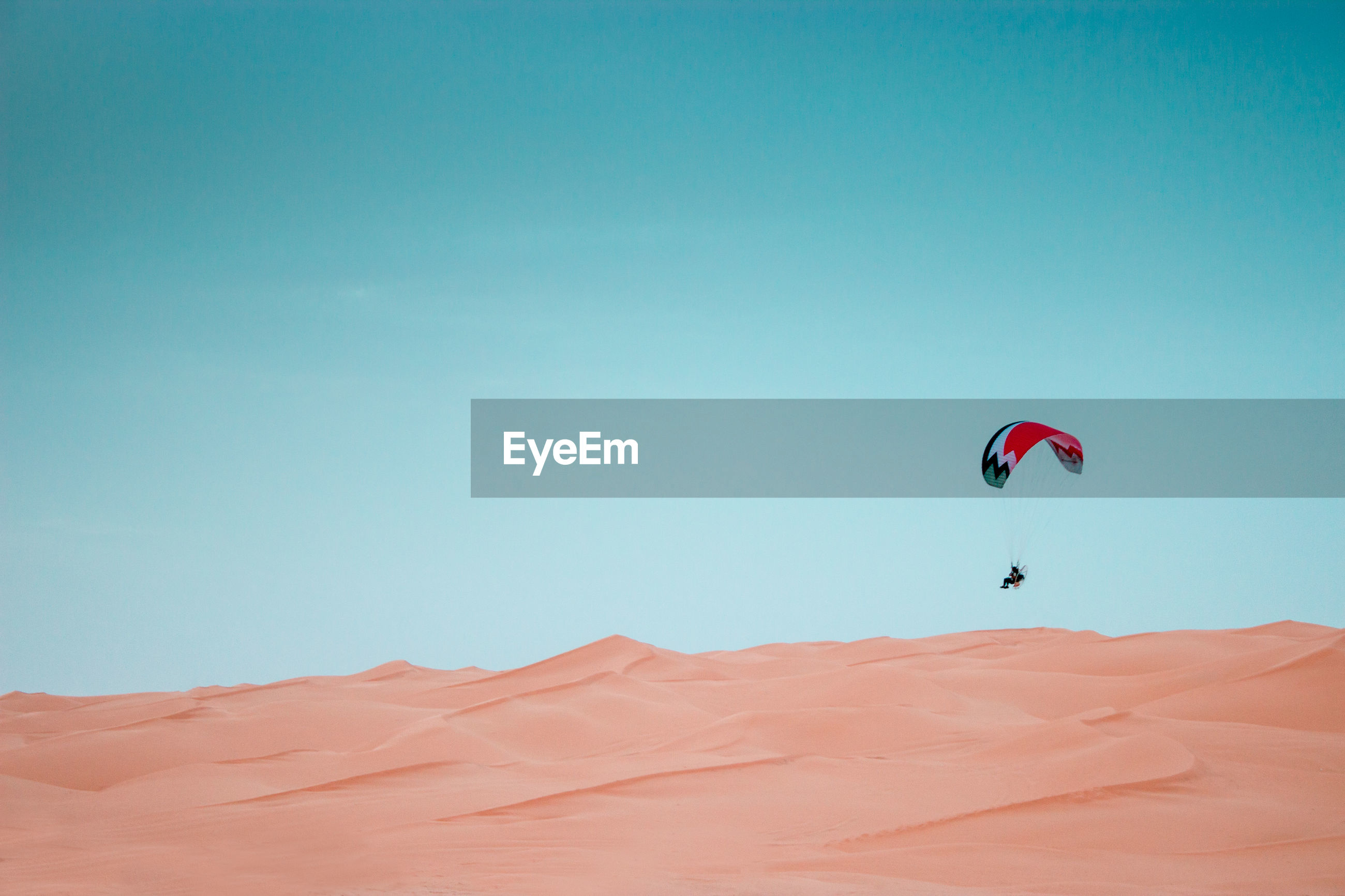 Person paragliding over sand dunes against blue sky