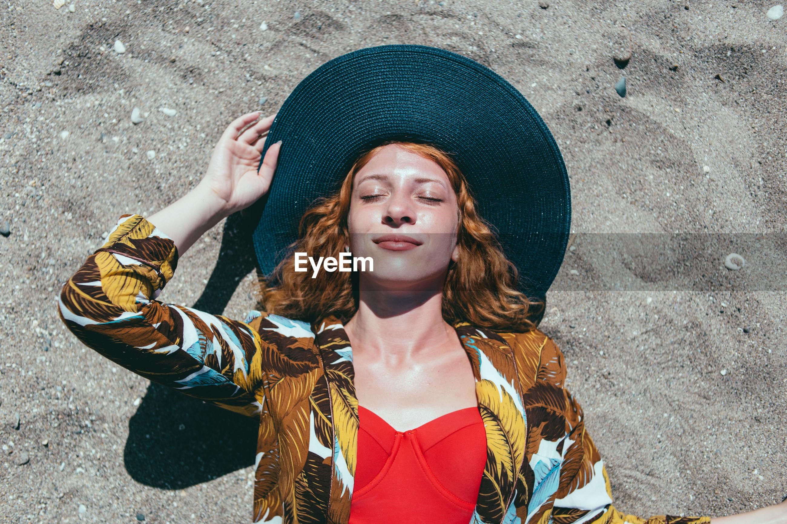 Woman in hat lying on beach