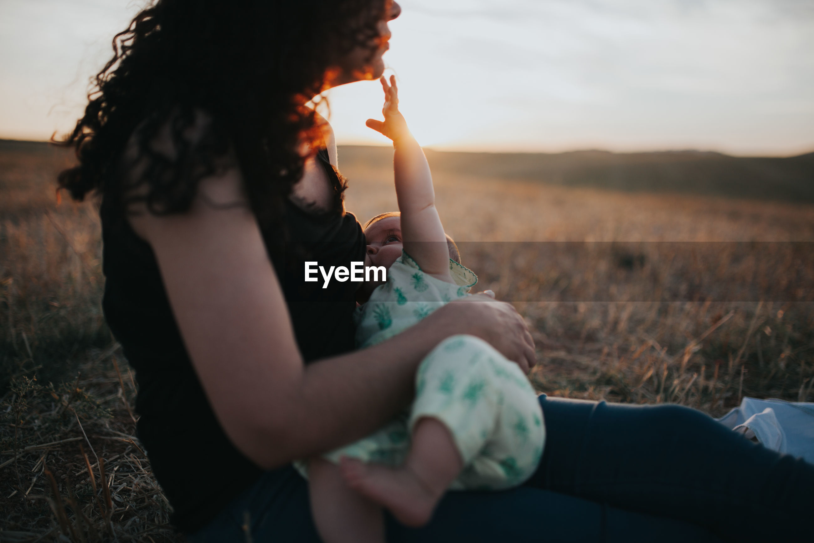 Side view of mother breastfeeding baby while sitting on field against sky during sunset