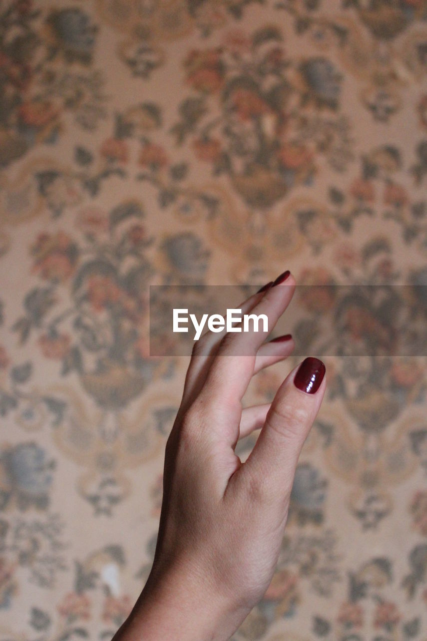 Cropped image of hand holding finger against blurred background