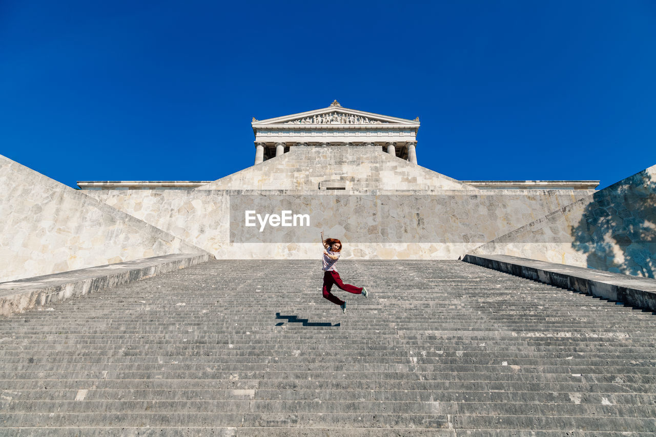 Low angle view of happy woman jumping on staircase against clear blue sky