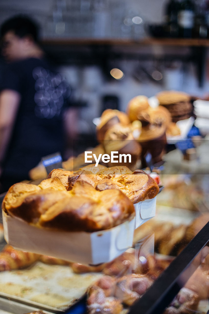 food and drink, food, freshness, incidental people, indoors, ready-to-eat, real people, focus on foreground, selective focus, occupation, baked, retail, sweet food, indulgence, dessert, kitchen, store, sweet, bakery, close-up, temptation, retail display, tray