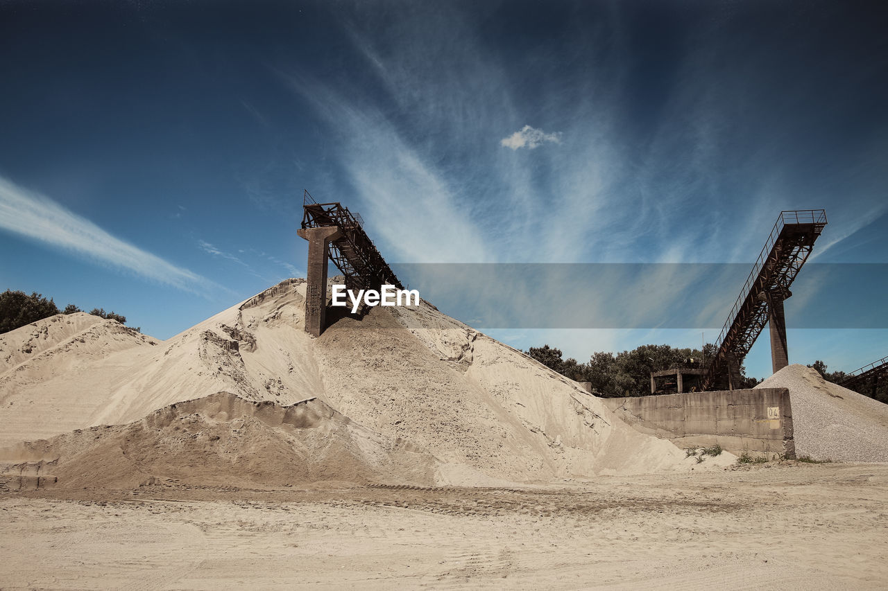 Low Angle View Of Conveyor Belt On Sand Pile At Mine Against Sky
