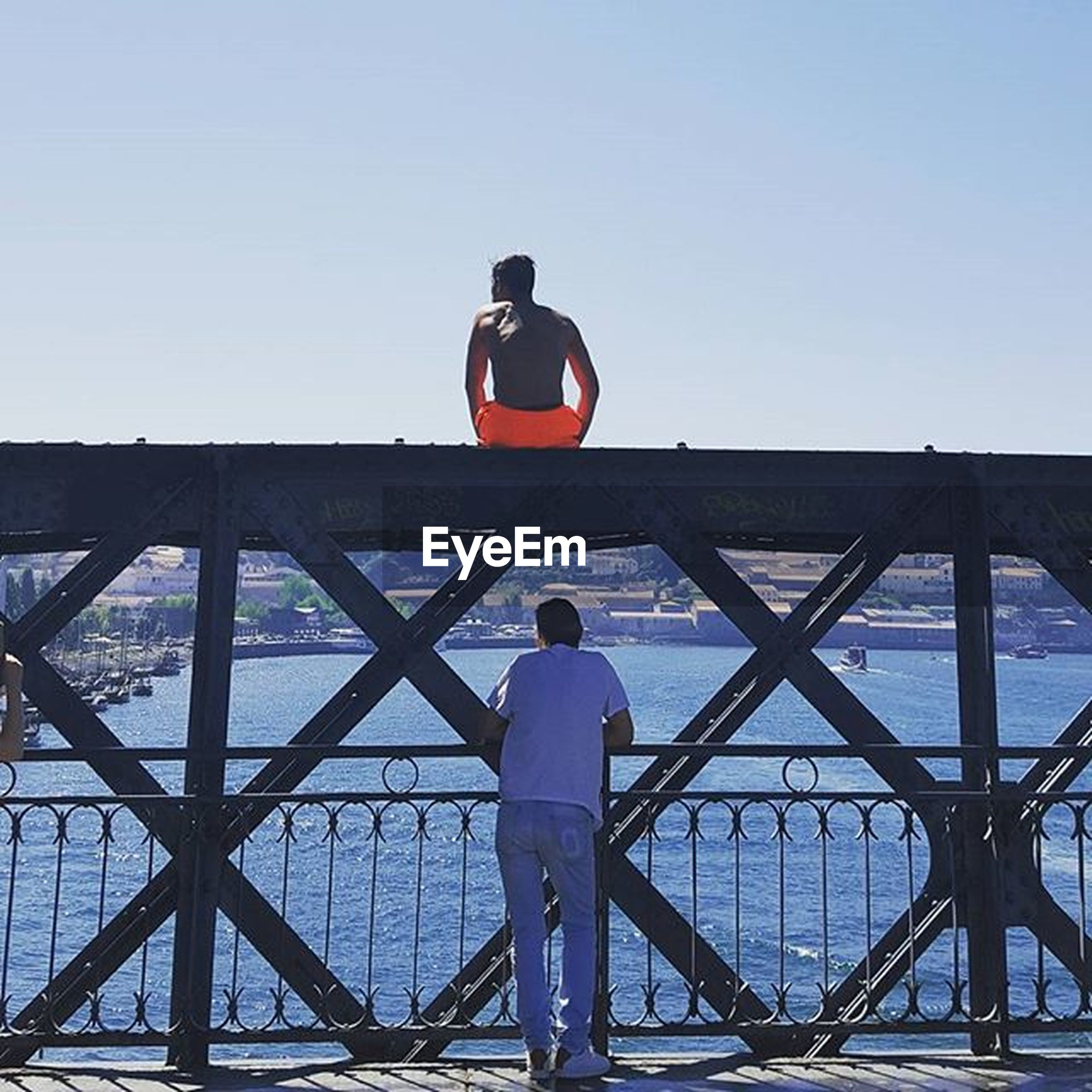 clear sky, lifestyles, railing, leisure activity, men, copy space, built structure, bridge - man made structure, full length, architecture, connection, transportation, rear view, standing, sky, blue, bridge, casual clothing