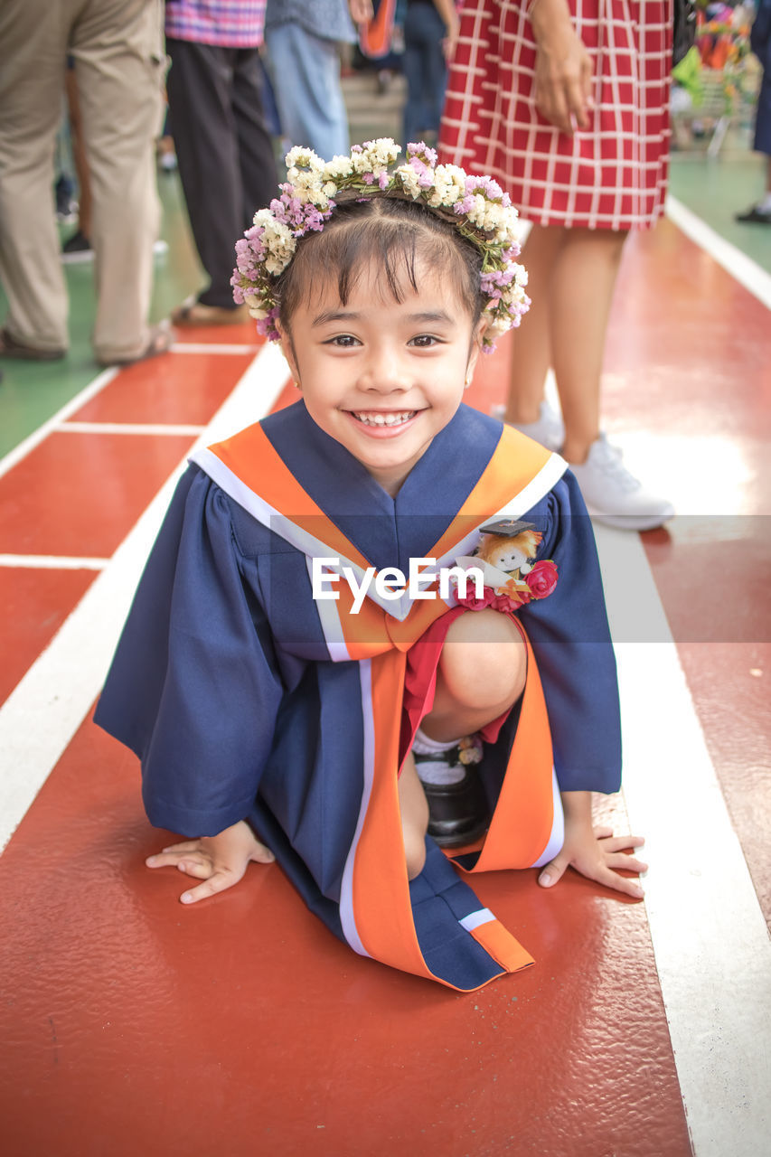 Portrait of smiling girl wearing flowers while kneeling on floor