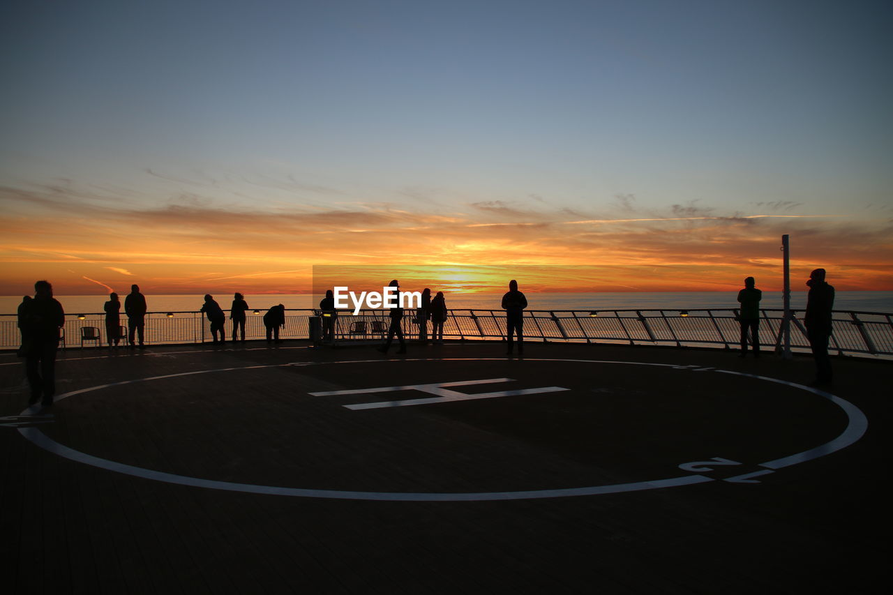 Silhouette of people on ship sky during sunset