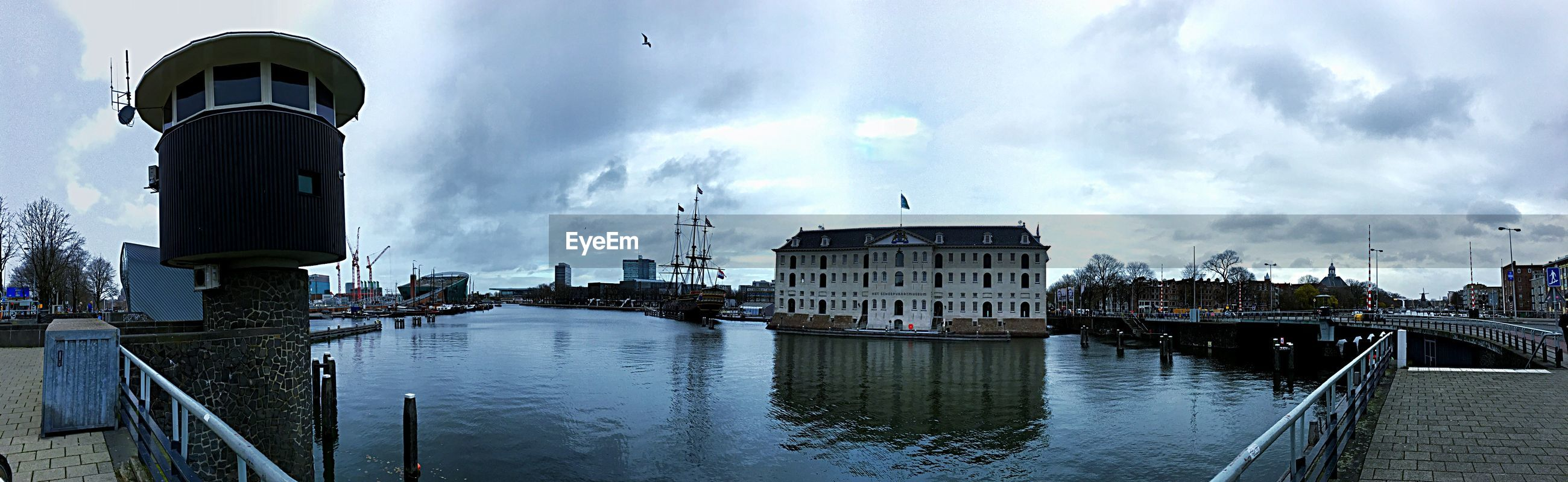 PANORAMIC VIEW OF BUILDINGS AND RIVER AGAINST SKY