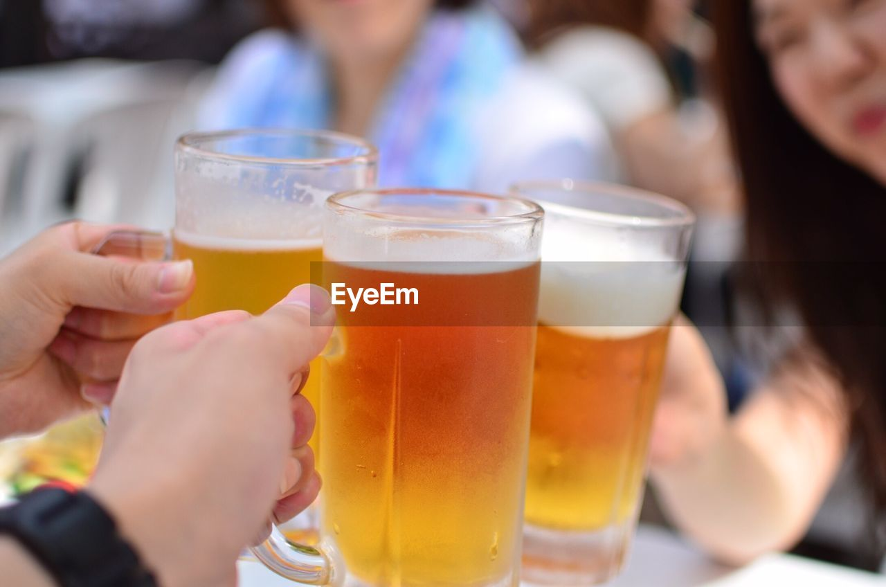 Cropped Image Of People Holding Beer Mugs