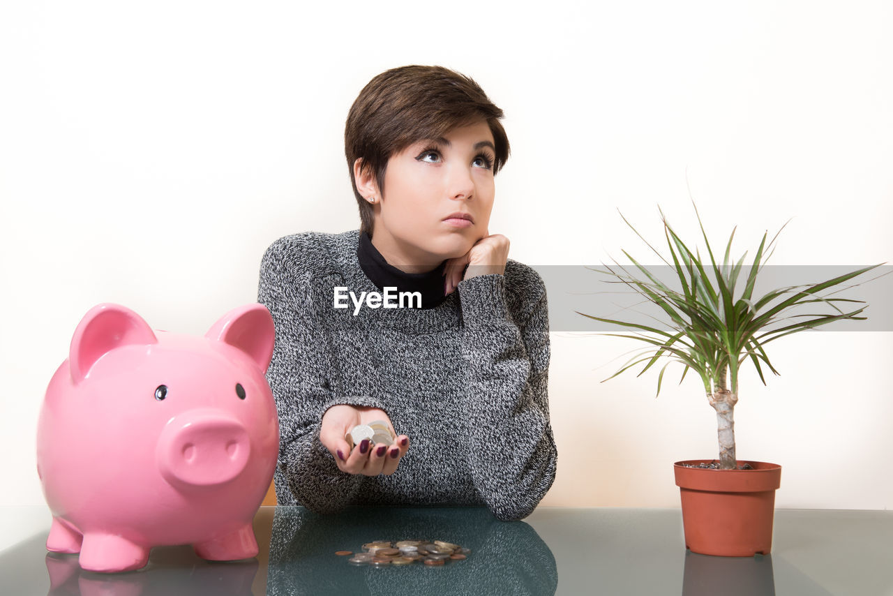 Young Woman Looking Up While Holding Coins By Piggy Bank Against Wall